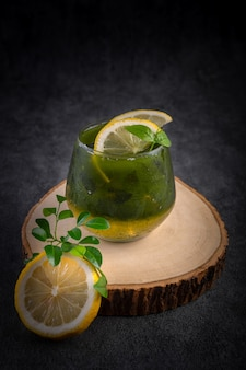 Cold lemon honey matcha decorated with lemon on a wooden cutting board