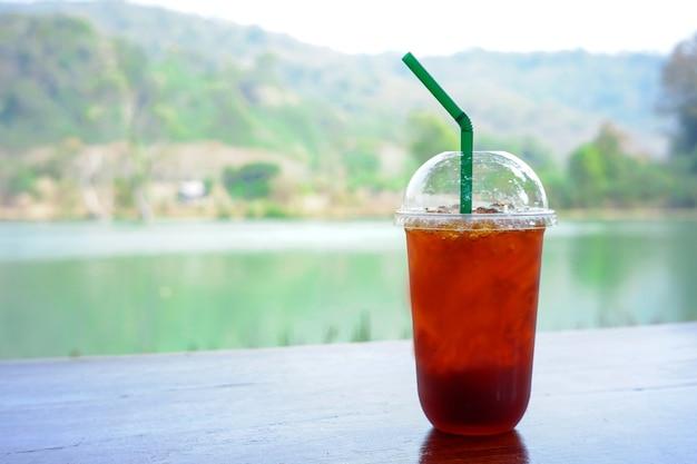 Холодный чай с лимоном в стакане, поставленный на деревянный стол с естественным фоном.