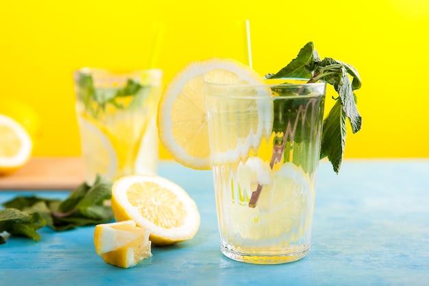 파란색 빈티지 책상에 노란색 배경 위에 더운 여름날을 위한 차가운 레몬 물 음료