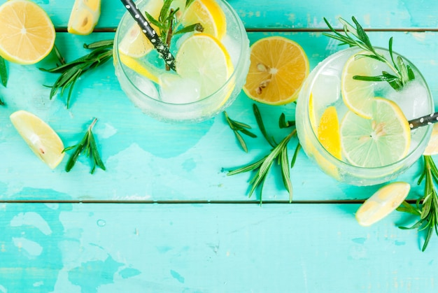 Cold lemonade or alcohol vodka cocktail with lemon and rosemary, on light blue table,  top view