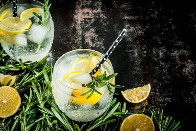 冷たいレモネードまたはアルコールウォッカカクテルレモンとローズマリー、黒さびた金属、トップビュー