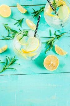 冷たいレモネードまたはアルコールウォッカカクテル、レモンとローズマリー、ライトブルーテーブル、トップビュー