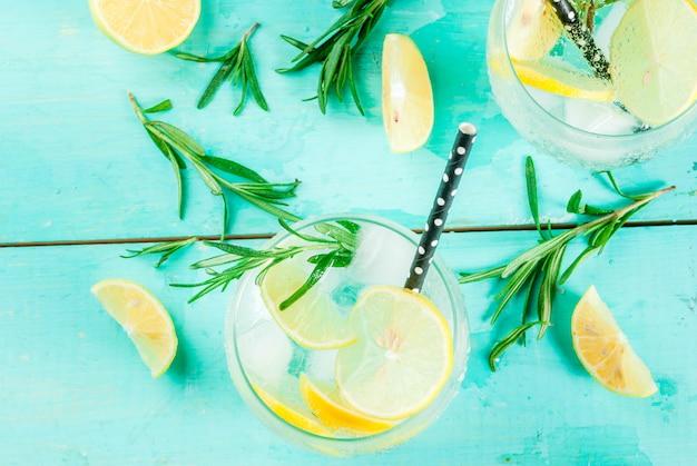冷たいレモネードまたはアルコールウォッカカクテル、レモンとローズマリー、明るい青のテーブルの上