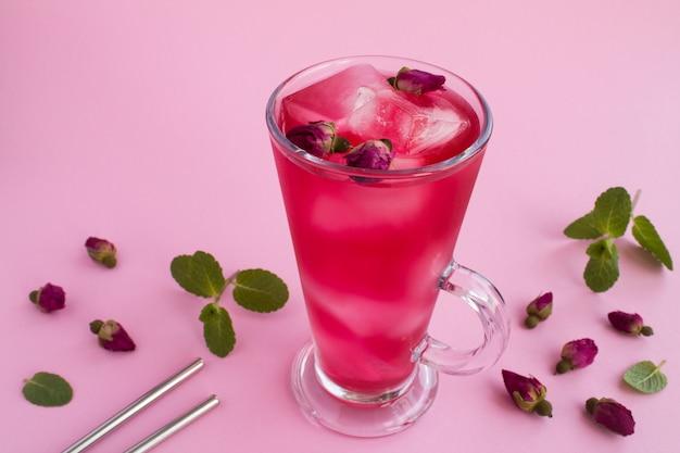 冷たいレモネードまたはピンクのテーブルにピンクのバラとお茶