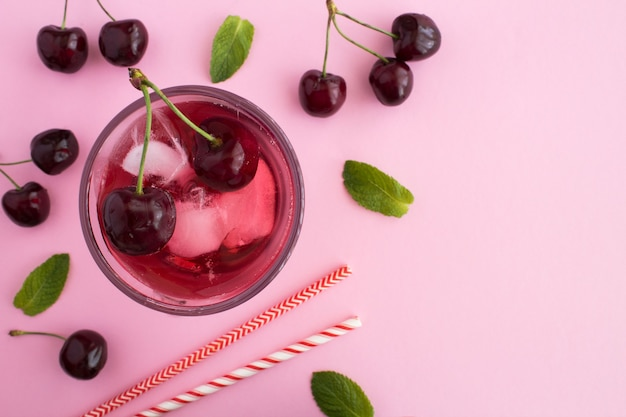 Cold lemonade with cherries the glass on the pink  background.top view.copy space.