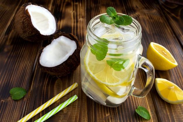 茶色の木製の背景にココナッツ、レモン、ミントと冷たいレモネード