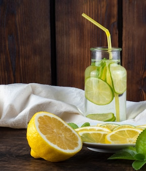 Cold lemonade with ice on wooden background