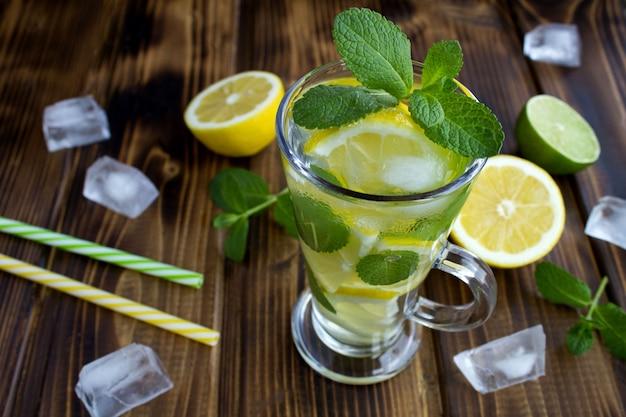 Холодный лимонад с лимоном и мятой в стекле на коричневой деревянной поверхности. крупный план.