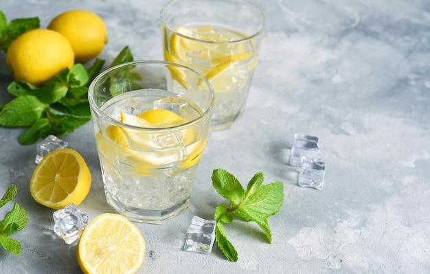 Холодный лимонад с лимоном, мятой и льдом на бетонном фоне.