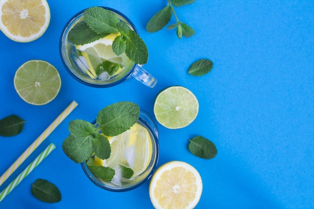 Cold lemonade with lemon and mint  in the glasses on the blue background.top view.copy space.