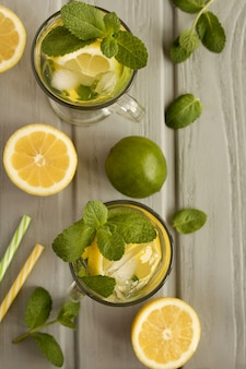 Cold lemonade with lemon and mint  in the glasses on the grey wooden background.top view.