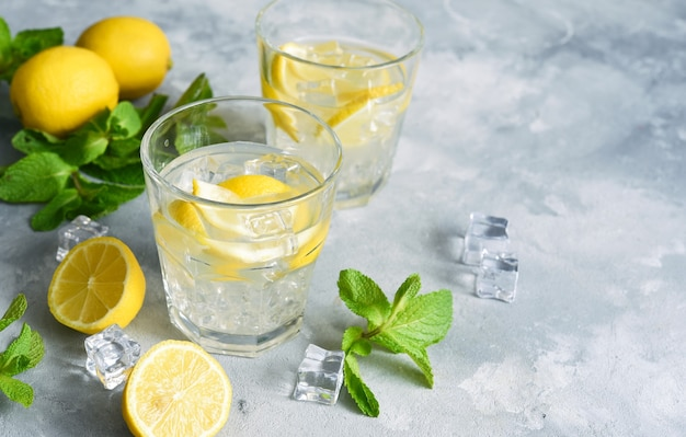 Cold lemonade with lemon, mint and ice on a concrete background.