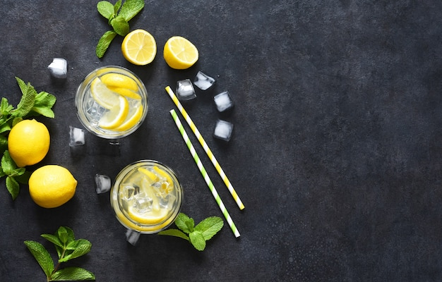 Cold lemonade with mint and ice on a black concrete background, top view.