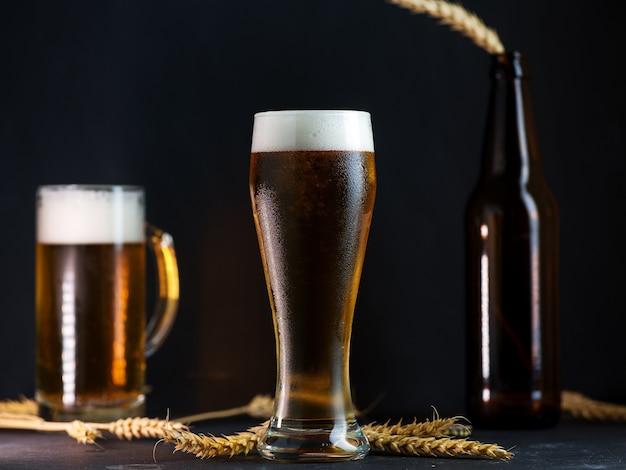 暗いテーブルの上のガラスの冷たい軽いビール