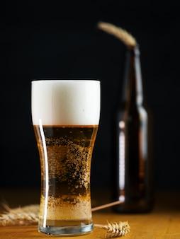 어두운 테이블에 있는 유리잔에 있는 차가운 라이트 맥주 라거를 닫습니다.