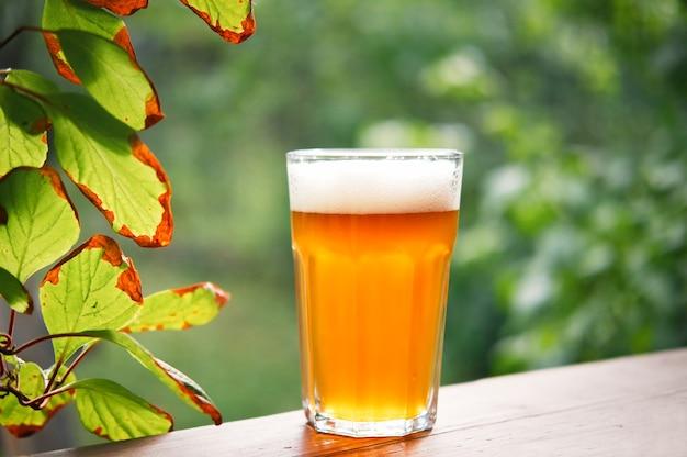 흐릿한 자연 배경을 가진 나무 테이블에 유리에 흰색 거품이 있는 차가운 가벼운 맥주.