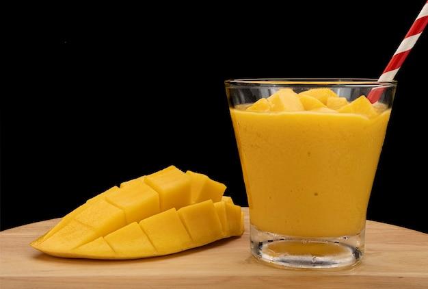 Холодный коктейль из манго с кубиками манго в бокале для коктейля на темном фоне.