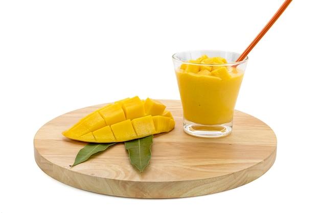 Холодный коктейль из манго с кубиками манго в бокале для коктейля на деревянной сервировочной доске.