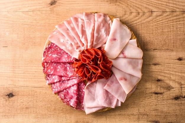 Холодное мясо на разделочной доске на деревянный стол ветчина, салями, колбаса мортаделла и индейка