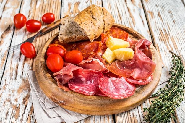 차가운 고기 접시, 나무 판자에 샤퀴테리 전통 스페인 타파스. 흰색 나무 배경입니다. 평면도.