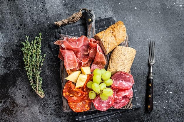 ハムプレート、豚肉-パンとブドウを添えた木の板に伝統的なスペインのタパス。黒の背景。上面図。