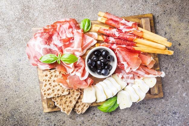 Тарелка холодного мяса с сыром, оливками и хлебом на разделочной доске над серым камнем