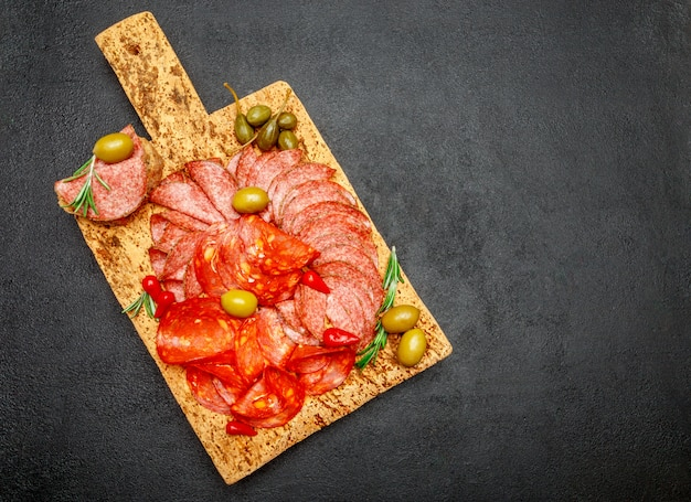 Cold meat plate with salami and chorizo sausage on cork wood board