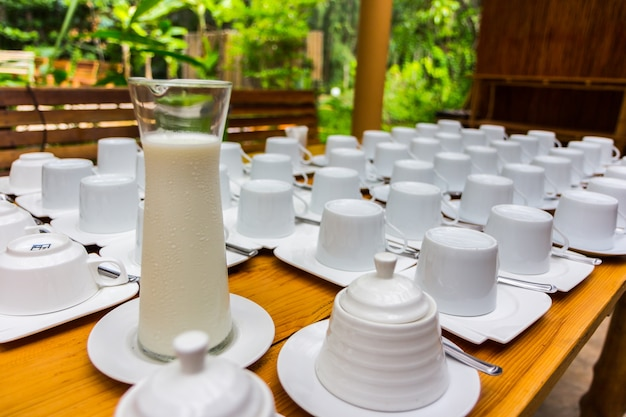 Cold milk in a jar and cup on the old wooden table in an outdoor