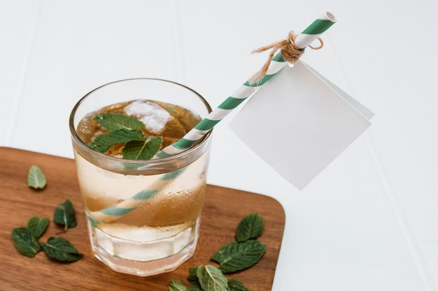 Cold mojito with mint and ice on wood plank with label for mockup