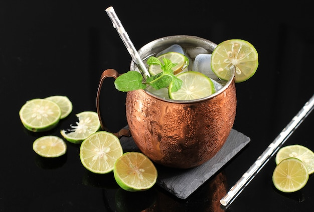 Холодный коктейль «московский мул» на медной кружке с имбирным пивом, лаймом и водкой, гарнир листом мяты. изолированные на фоне черного сланца. копировать пространство для текста