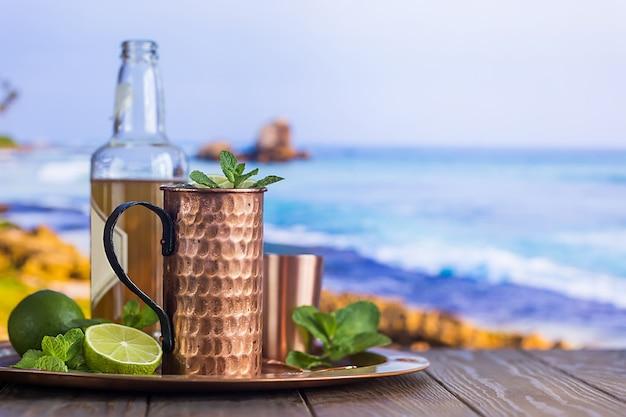 冷たいモスコミュールのカクテル、ジンジャービール、ウォッカ、ライムをビーチと海辺の表面に。