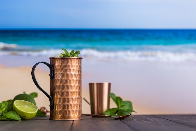 Cold moscow mules cocktail with ginger beer, vodka and lime over beach and seaside background