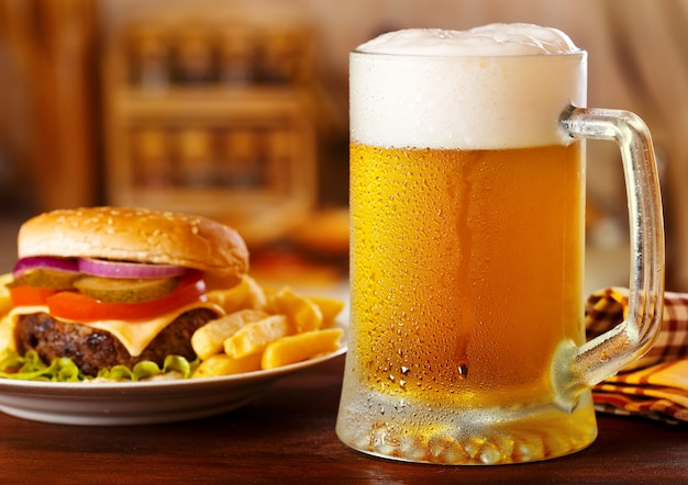 Cold mug of beer with hamburger on wooden table