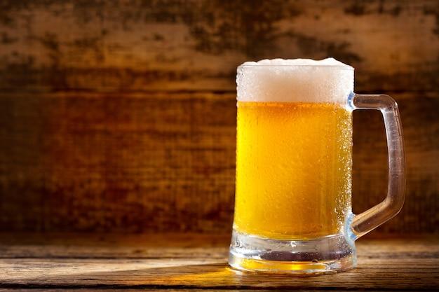 木製のテーブルに冷たいビールのマグカップ