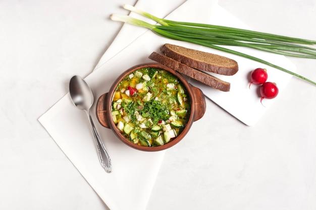 粘土のカップに新鮮な野菜と肉が入った冷たいオクローシカが灰色の上に立っています