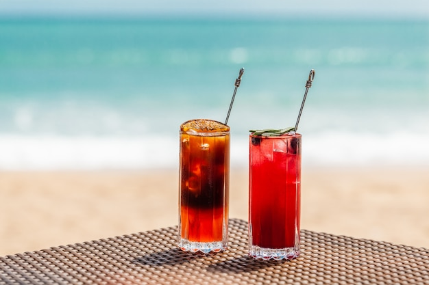 Холодные апельсиновые и малиновые коктейли на столе на пляже солнечного моря на фоне