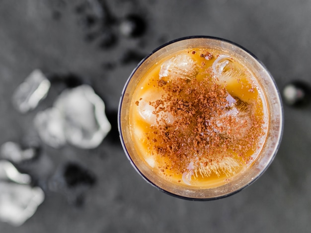 Cold orange cocktail with ice and cinnamon