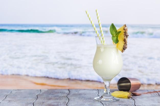 Холодный коктейль пина колада в стакане на пляже с поверхностью морского пейзажа