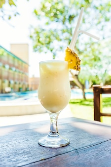 Холодный коктейль пина колада в стакане на столе в кафе на открытом воздухе