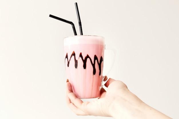 Cold pink milkshake in glass mug on. cocktail holds female hand. minimalism.