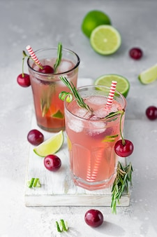 Cold pink non-alcohol cocktail with cherries, lime and rosemary on light wooden cutting board.