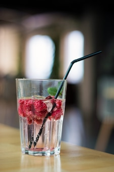 Cold raspberry drink with mint leaves in a sweaty glass on a table in a cafe
