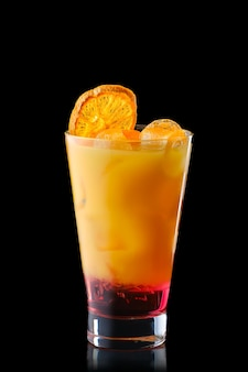 Cold refreching cocktail with orange juice and cherry syrup isolated on black background