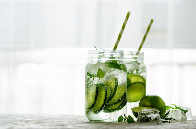 Cold and refreshing detox water with lime, cucumber, rosemary and ice in glass jar. copyspace.