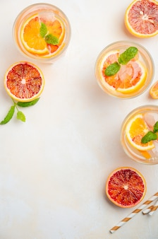 Cold refreshing drink with blood orange slices in a glass on a white concrete background