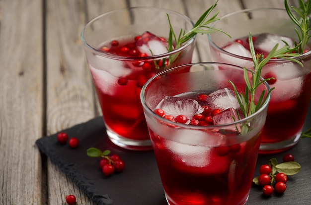 Cold refreshing drink with cranberries and rosemary on a wooden background.