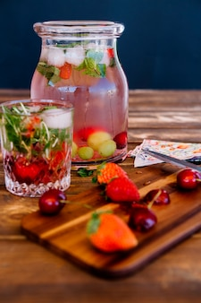 Cold refreshing drink with strawberries and mint in jar