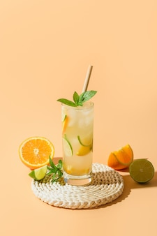 Cold and refreshing lemonade or cocktail with orange and lime slice.