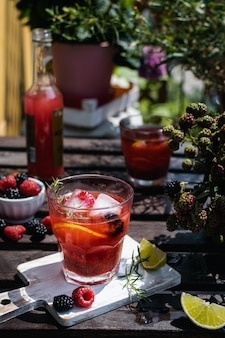 Cold refreshing lime, blackberry and raspberry lemonade with ice on wooden rustic table