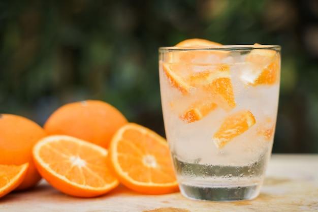 Cold and refreshing orange soda with orange slice on wood